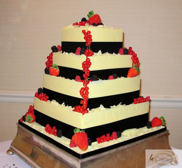 4 Tier Ivory Chocolate Wedding Cake decorated with black ribbon and ...