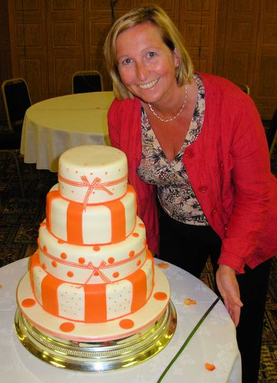 Sian with a 4 Tier Creme & Orange Wedding Cake