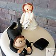 Wedding cake topper with bride, groom and X box