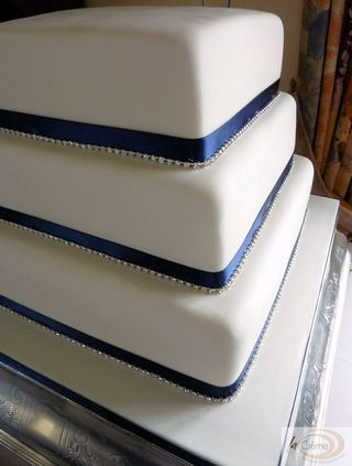 3 tier ivory wedding cake with blue ribbons and diamantees S